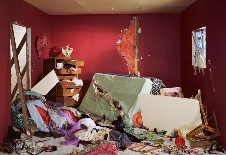 A bedroom in a state of disarray, the ground covered with clothing and a shredded mattress.