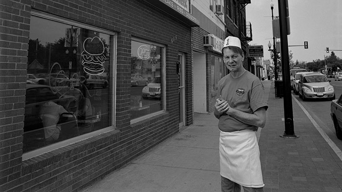 Man wearing apron outside of a burger shop