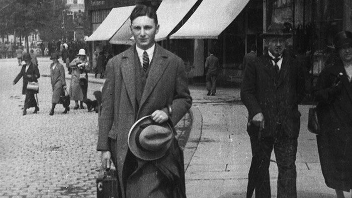 Old photograph of a man on the sidewalk holding his briefcase and hat