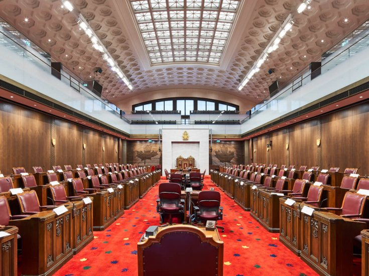 The senate chamber with red carpeting and wood panelled walls.