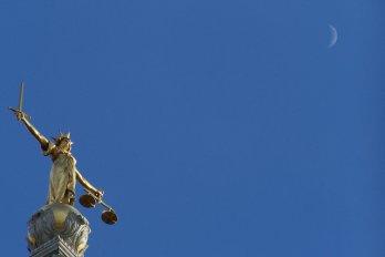 Statue symbolizing justice beneath a crescent moon