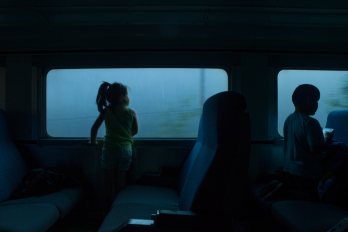 girl looking out the window of a moving train
