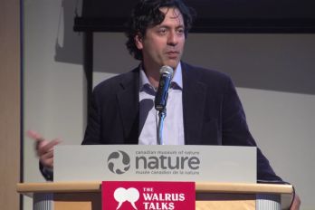 Man speaking in front of crowd at the walrus talks