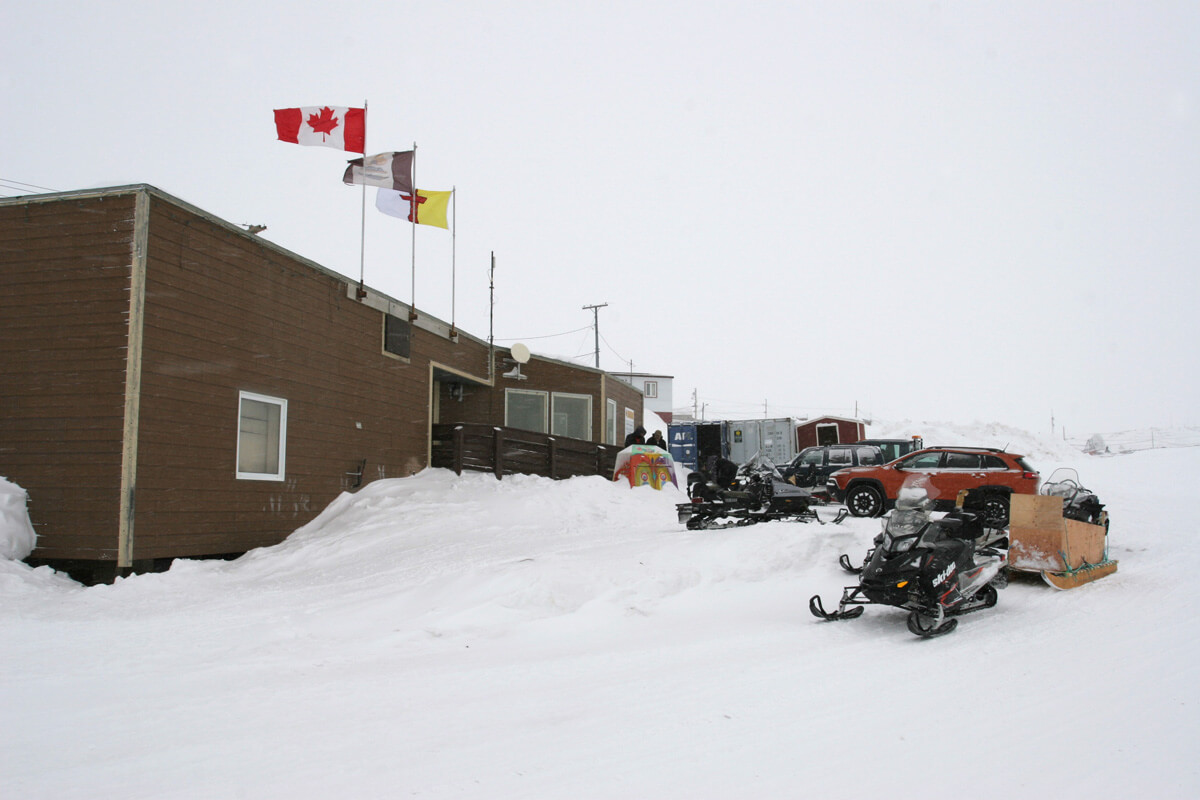 The hamlet office, flying the flags of Cape Dorset, Nunavut, and Canada.