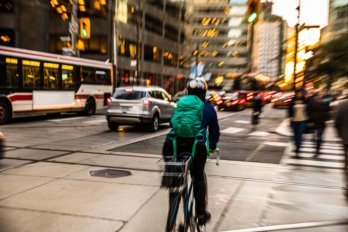 A cyclist crossing a busy intersection in downtown Toronto at dusk. The streets are full of cars and a TTC bus. In the background are high-rise office buildings.