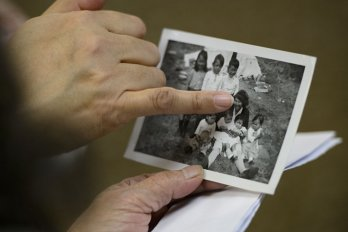 A pair of hands points at a black and white photo containing a woman and seven young children.