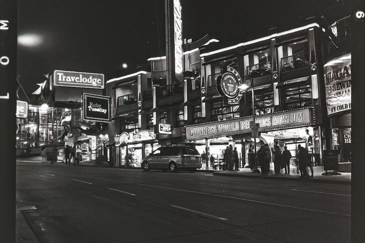 A black and white shot of Clifton Hill's storefronts at night. Visible signs include a Travelodge, a Ruby Tuesday, and the Guinness World Records Museum.