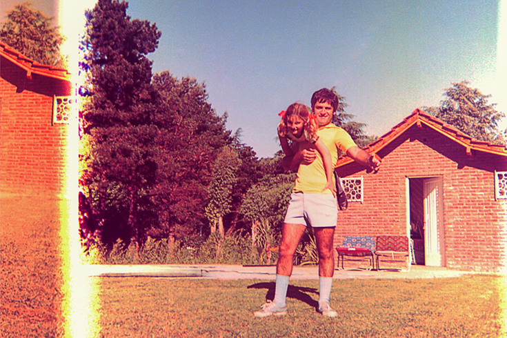 Vintage and damaged photo of a girl and her father playing outdoors. The father is wearing a yellow shirt and shorts and carrying his daughter, a child with pigtails. They are standing in front of a bungalow with an open door.