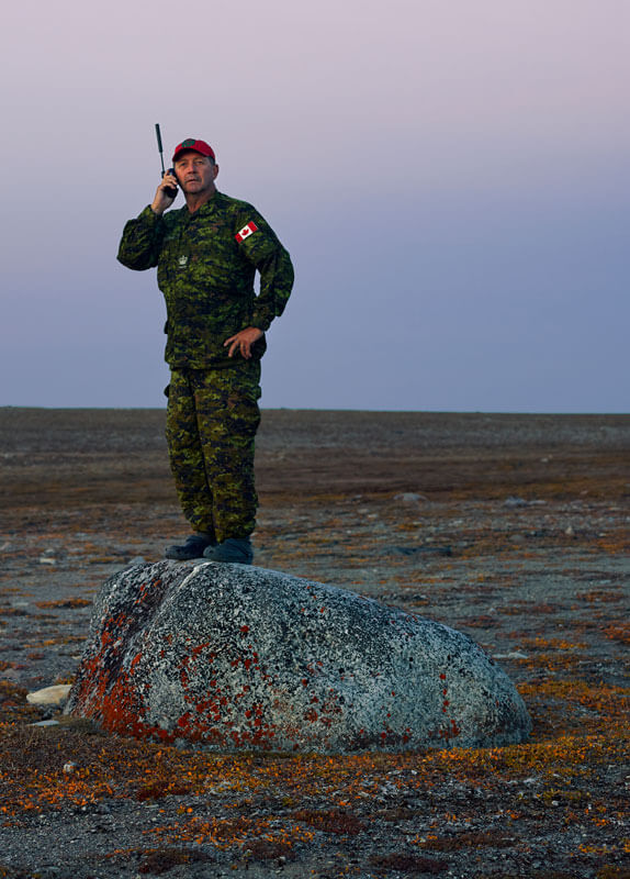 Man in a Canadian combat uniform holds a remote phone to his ear while standing on a rock.