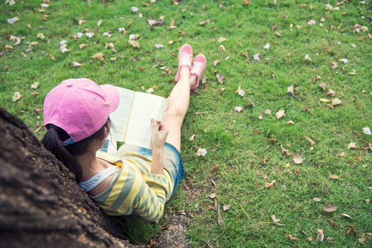 A girl with black hair reads a book while sitting under a tree.
