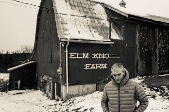 "A black and white photo of an older man wearing a winter coat, his hands in his pockets. Behind him is a barn that says ""Elm Knoll Farm"" and the ground is covered in snow."