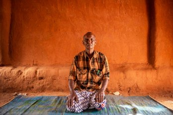 Photograph of a man kneeling on a woven mat in front of an orange wall.