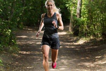 A woman marathoner running in the woods.