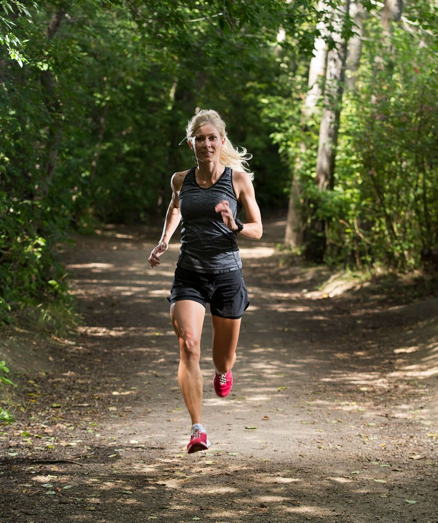 A woman marathoner running in the woods.