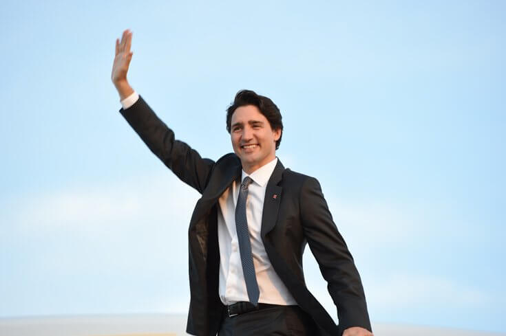 Justin Trudeau wearing a suit and waving against the backdrop of a blue sky.