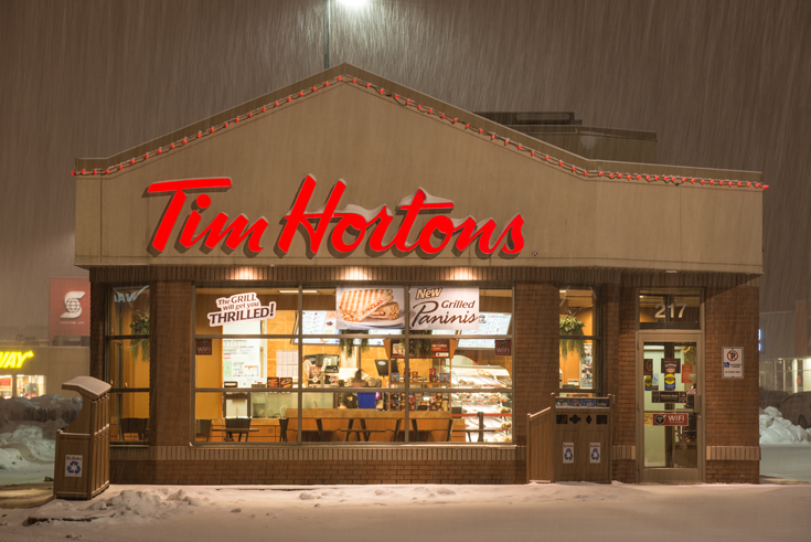 A photo of a Tim Hortons retail store and drive through during a heavy snowfall.
