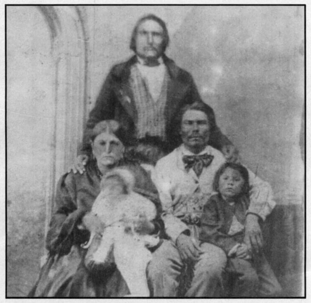 Abraham Salois, the author's Metis ancestor, standing behind his family.