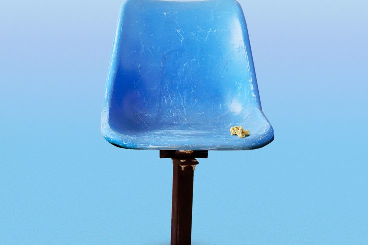 A blue plastic sports arena chair, empty but for a few pieces of popcorn. Several pieces of popcorn are on the ground. The background is light blue.