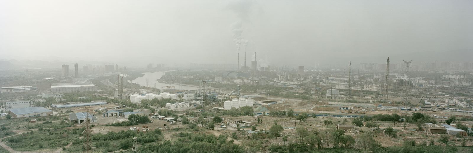 A wide view of the city of Lanzhou, which is very industrial with a hazy sky.