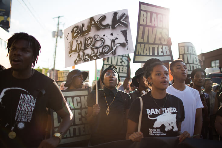 A crowd of protestors marches toward camera, carrying Black Lives Matter signs.