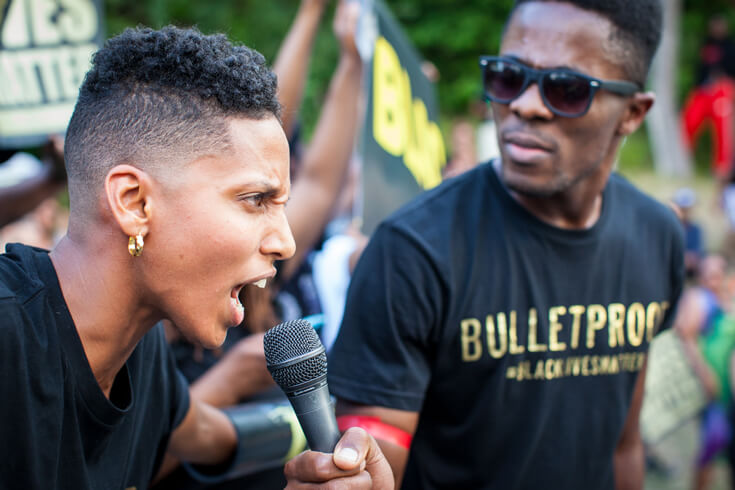 Janaya Khan, a leading organizer of Black Lives Matter Toronto, speaks into a microphone as a fellow protestor holds it up.