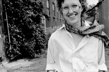 A photograph of the poet, Bronwen Wallace, in black and white. She is wearing jeans, a white shirt, and a scarf tied around her neck. Her hands are in her pockets and she is smiling at the camera.