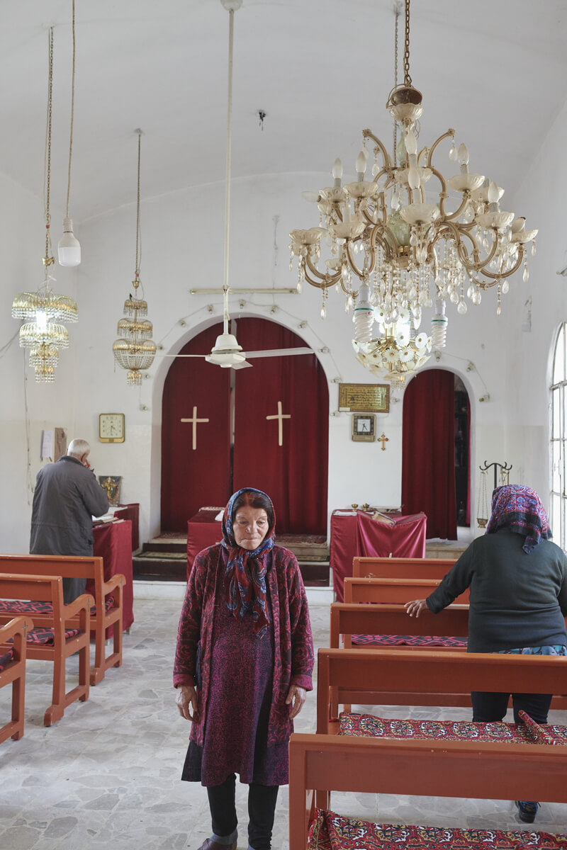 A woman facing the camera with her back to the altar in a Christian church. On either side of her are two people facing the altar and praying.