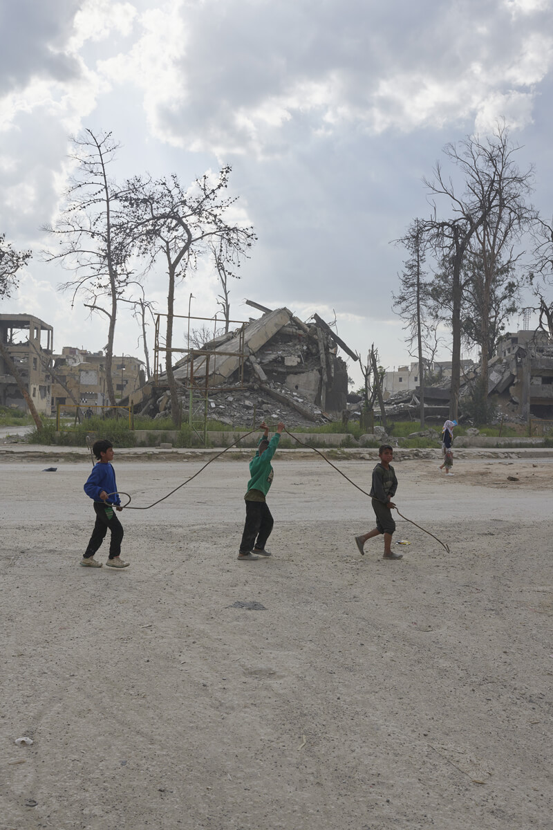 A line of three young children playing in a bare field in front of building rubble.