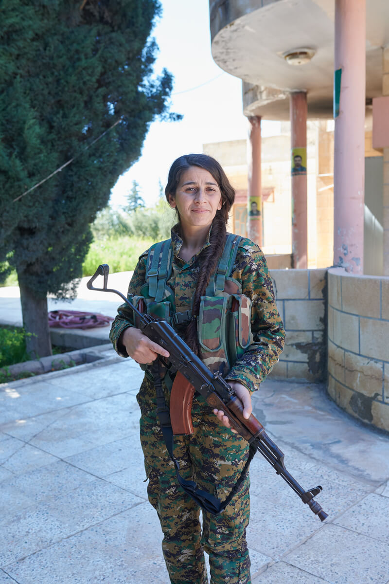 A woman wearing military fatigues and carrying a rifle faces the camera.
