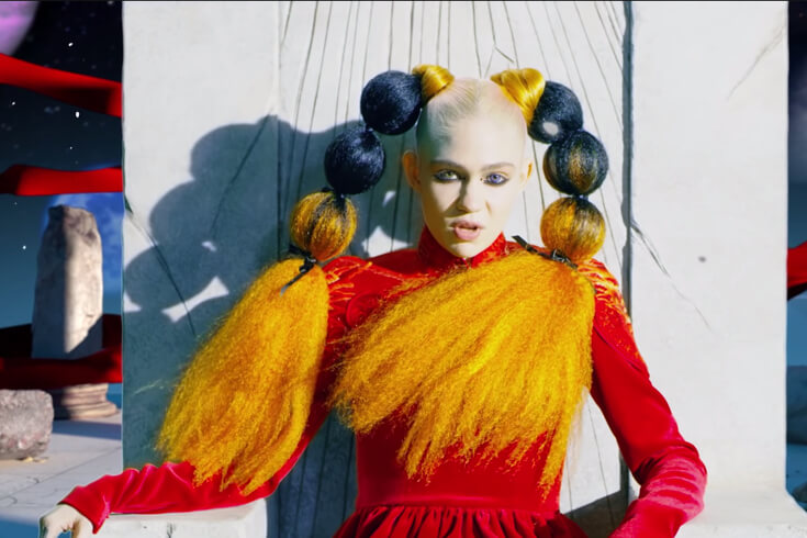 The singer Grimes, wearing a red velvet dress and with her hair in puffy orange-and-black pigtails, sits on a concrete throne and stares at the screen.