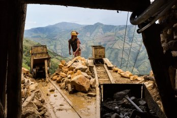 A miner stands at the end of a shaft by the mining cart track, with mountains in the background.