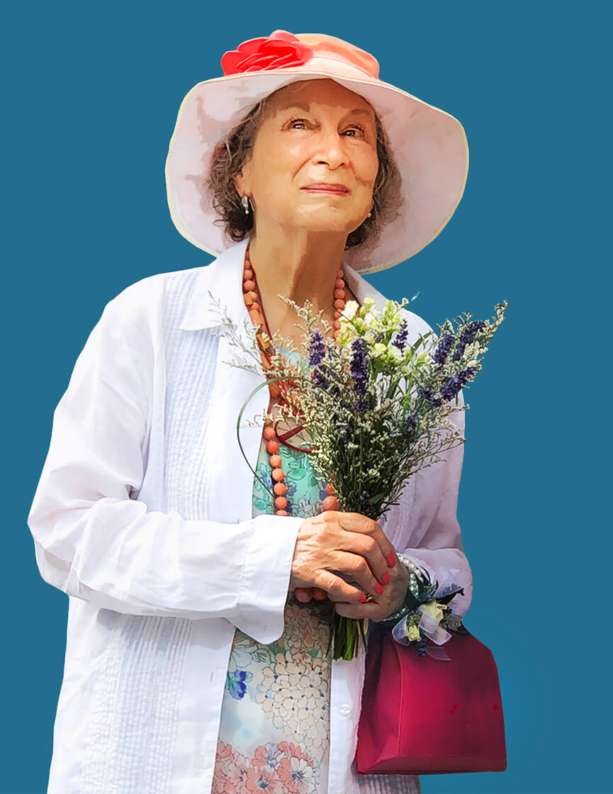 A photo of Margaret Atwood, wearing a floppy white hat and clutching a bouquet of flowers against a dark blue background.