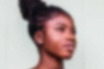 A photo of a Black woman with her hair in a bun, looking to the right of the frame. The image is slightly blurred.