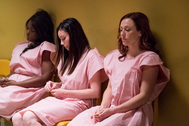 three women wait in hospital gowns