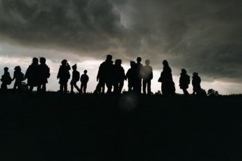 Group of people standings in a field at sundown