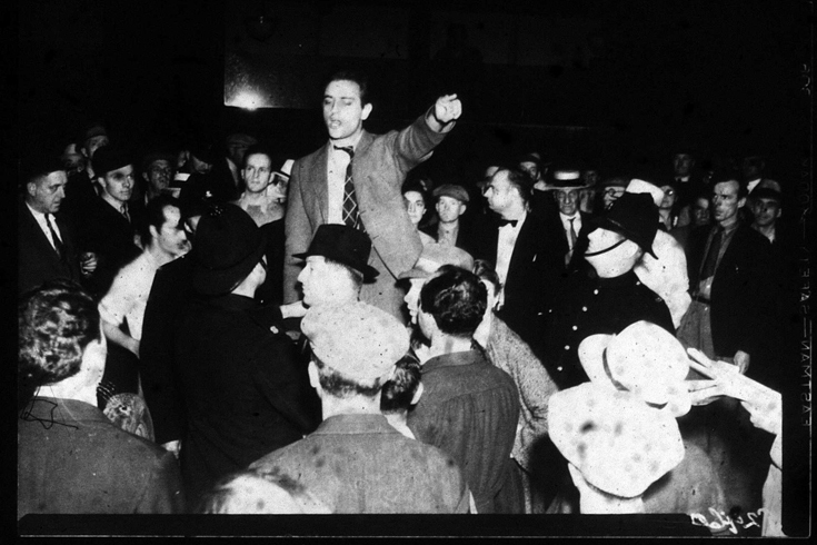 A man in a suit stands in the middle of a crowd, slightly elevated. He is pointing his finger as he addresses the crowd.