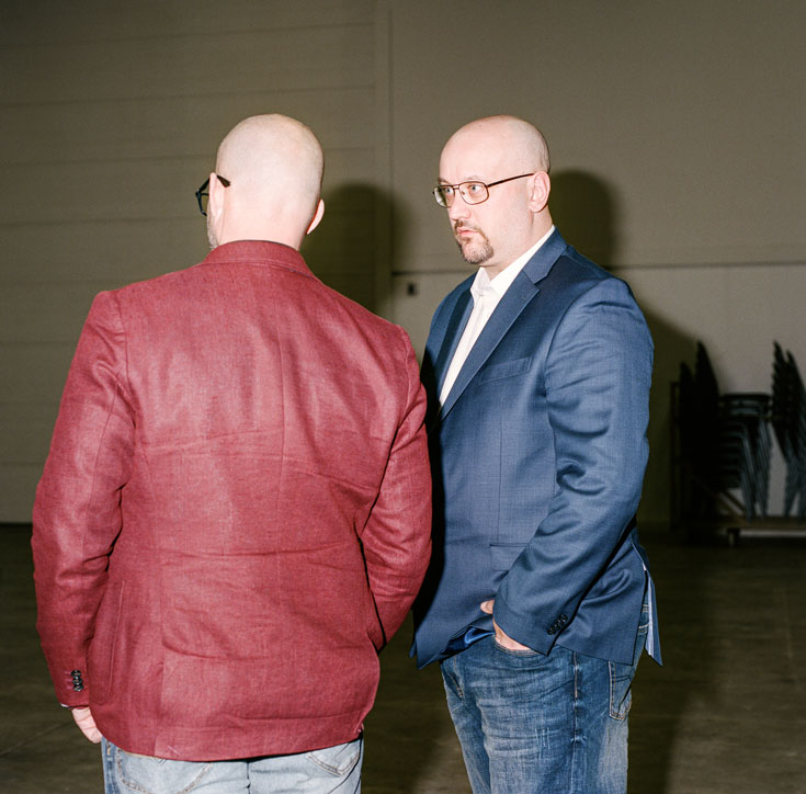 Two bald men are in conversation, one with his back to the camera wearing a red jacket. The other has a goatee and is wearing a blue blazer and jeans.