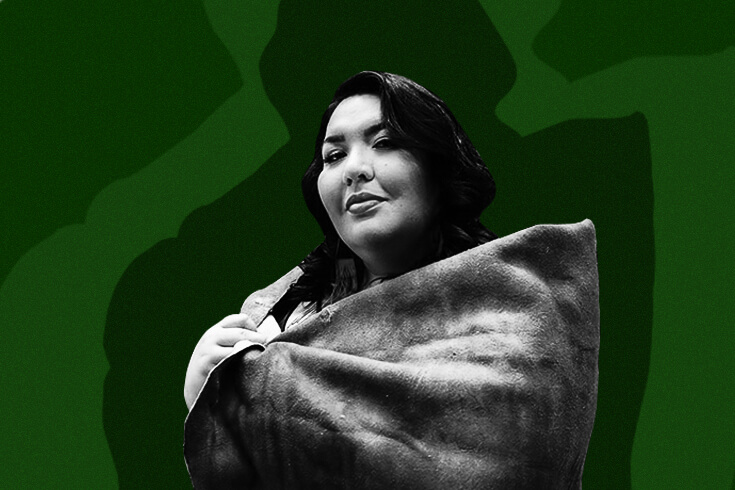Tenille Campbell, the poet, smiles at the camera while wrapped in a shawl against a forest-green background.