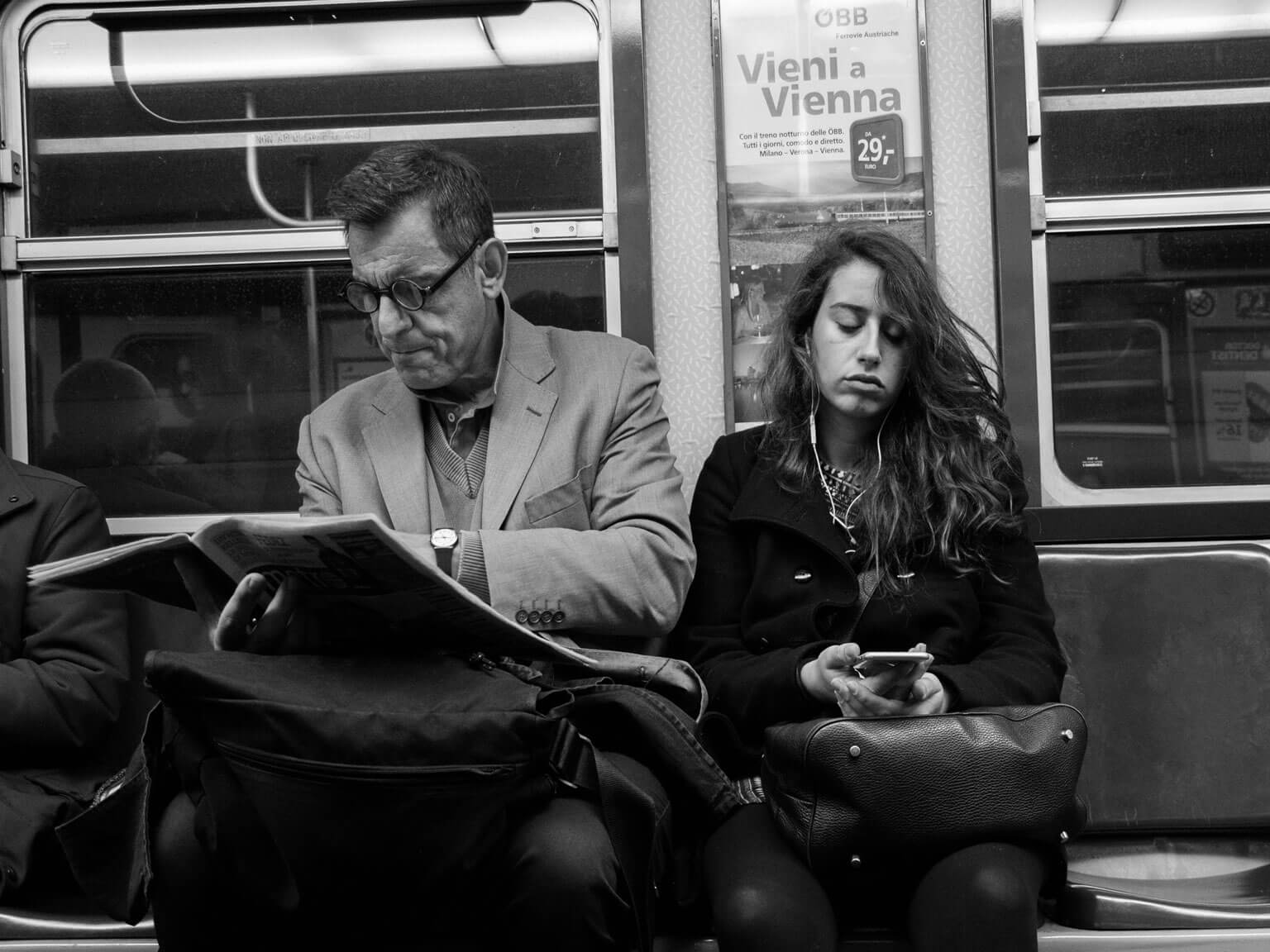 An older man reads a newspaper while a younger woman reads on a smartphone