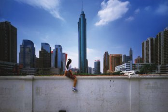 woman sits on a wall in shenzhen china