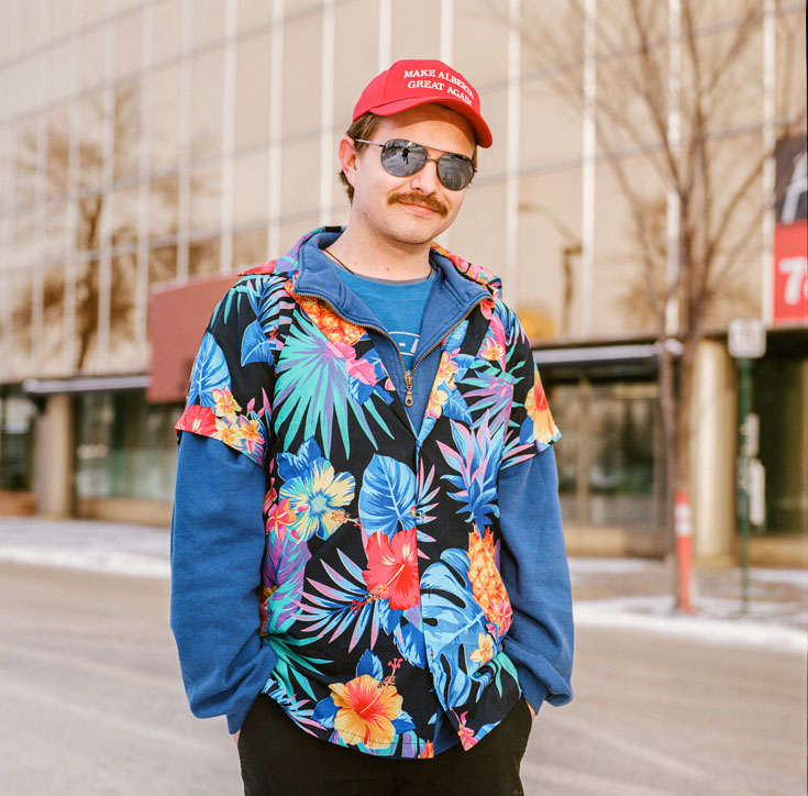 "A young mustachioed man wearing aviator sunglasses, a Hawaiian shirt over a blue sweatshirt, and a red hat that reads ""Make Alberta Great Again"" smiles at the camera."