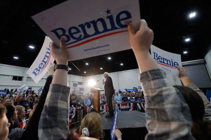 "Bernie Sanders stands on a stage at a podium, surrounded by a crowd, many of whom are hoisting ""Bernie"" signs in the foreground of the photo."
