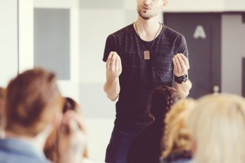A man stands at the front of a classroom wearing a dark t-shirt and lecturing. The photo focuses on his hands and torso.