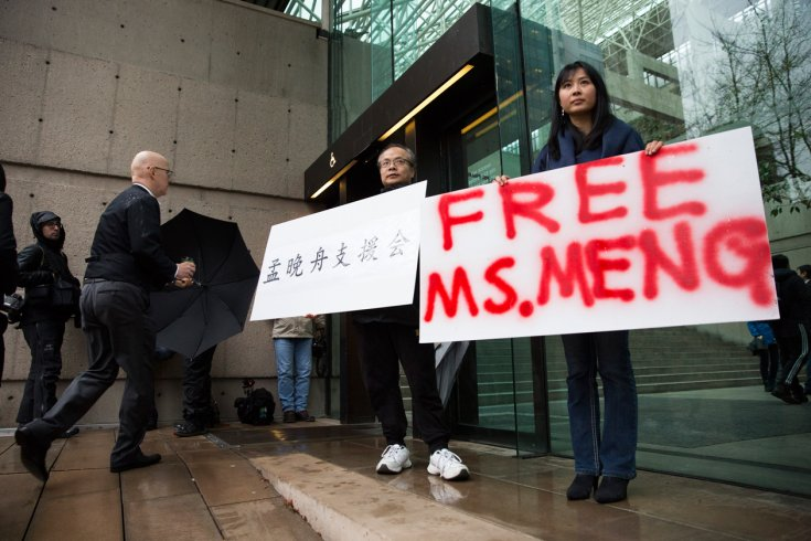 "Two people hold signs outside a courthouse. One reads ""Free Ms. Meng."""