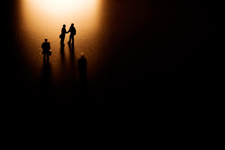 Two people shaking hands under a spotlight, surrounded by darkness