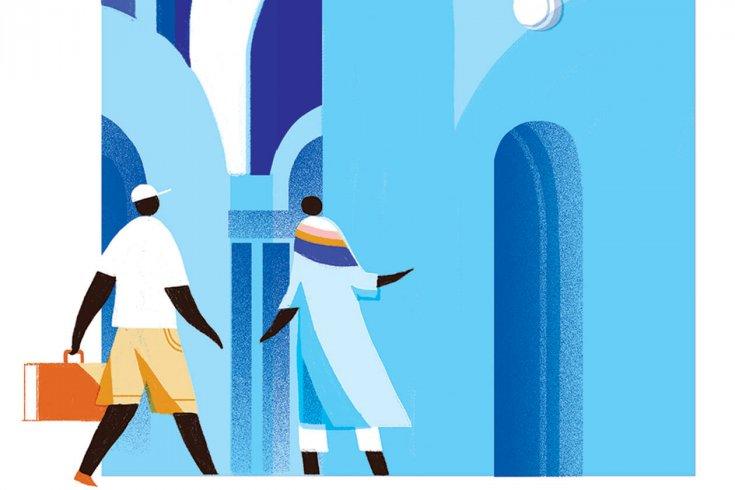 Two people walking near a blue building