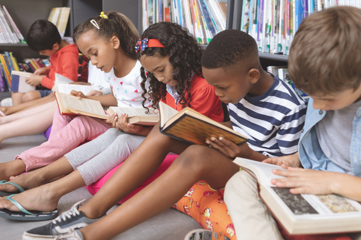 A row of children sit in front of a bookcase and read books studiously.