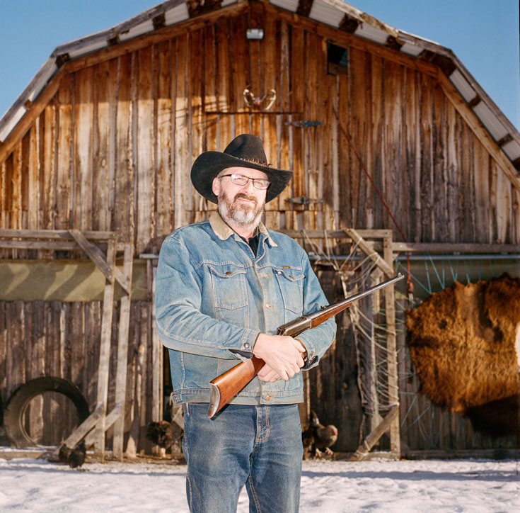 A bearded man stands in front of a barn and carries a rifle. He is wearing blue denim and a brown cowboy hat.