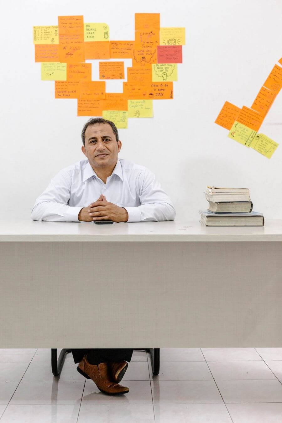 Mohamad Al-Radhi, sitting at desk with wall of sticky notes behind