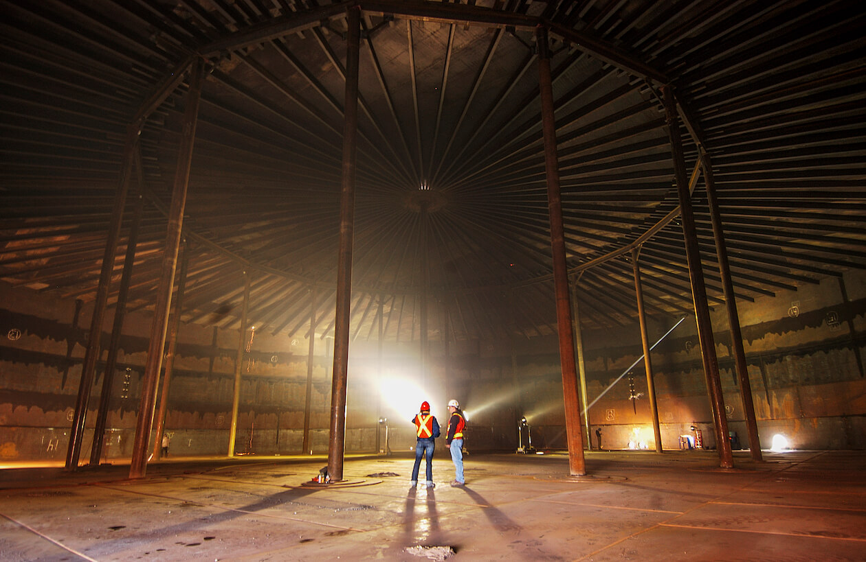 Two men stand inside an empty fuel container at Yellowknife's tank farm.